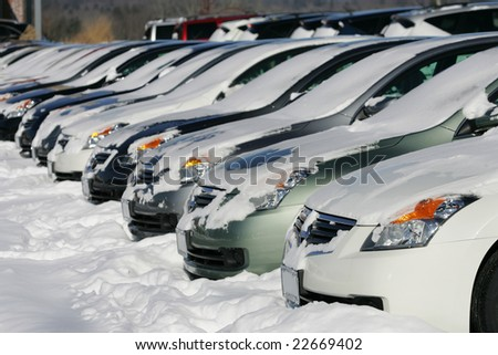 A row of cars covered in snow at a car dealership after a snow storm