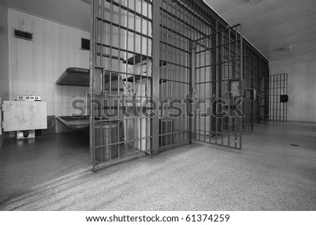 A row of 5 cells in an old jail.  The iron doors are heavy and the ammenities are few.