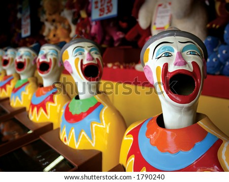 A row of clowns at an amusement park game.