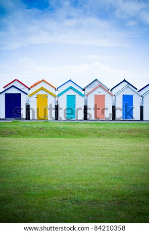 A Row of colorful beach huts stretching along a seafront with blue sky behind.