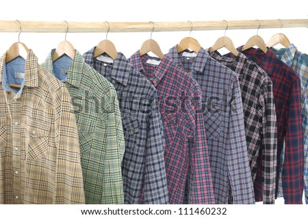 A row of colorful row shirts hanging on hangers on a white background