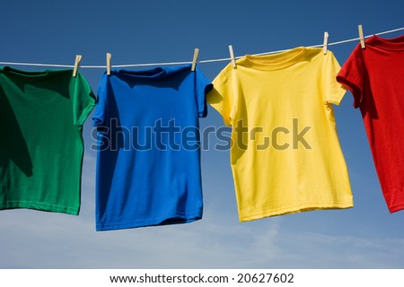 A row of colorful row t-shirts hanging on hangers on a blue sky background #20627602