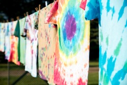 A row of colorful tie-dye T-shirts hanging outside on a clothesline in the sun