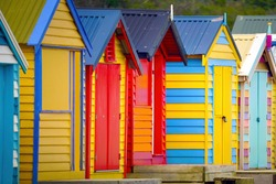 A row of colourful multi-coloured wooden beach huts at Brighton Beach, Melbourne, Victoria State, Australia
