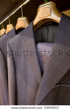A row of designer suits hanging in a menswear store. Made in Italy