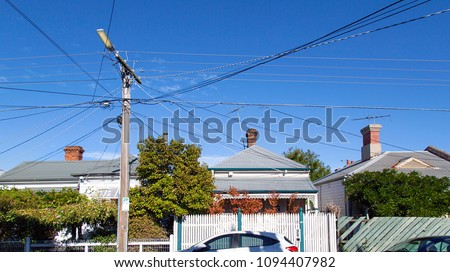 A row of detached houses in a St Kilda suburb. A telegraph pole has many crossing over cables running into the houses on the street.