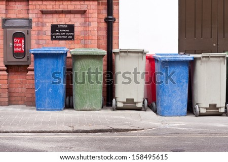 A row of different coloured wheelie bins