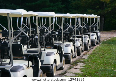 A row of empty golf carts at a country club.