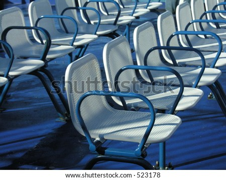 A row of empty seats on the upper deck of a ferry.