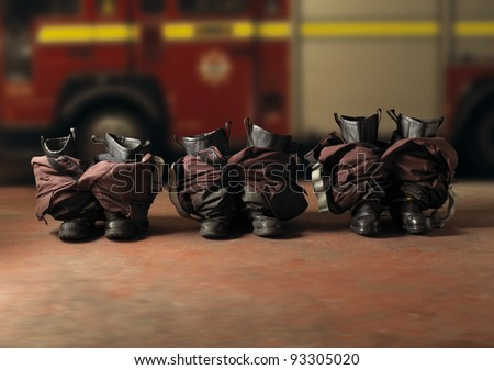 A row of fireman boots at the ready with a fire engine in the background