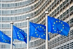 A row of flags of the European Union blowing in the wind in front of the Berlaymont building, headquarters of the European Commission, the executive of the European Union (EU) in Brussels, Belgium.