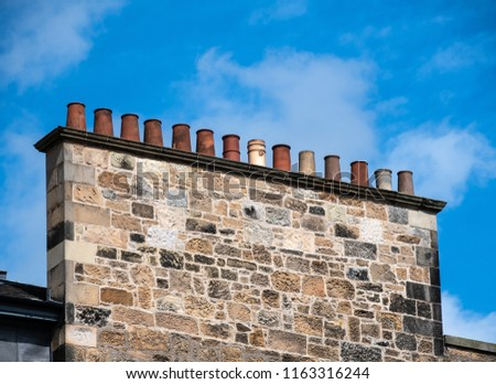 A row of fourteen chimney pots atop a single stack #1163316244