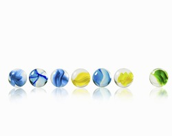 A row of glass marbles of different patterns and colours, with one separated from the rest.