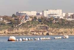 A row of large iron barrels for mooring ships. Buoys on the background of the city of Sevastopol inside the bay.