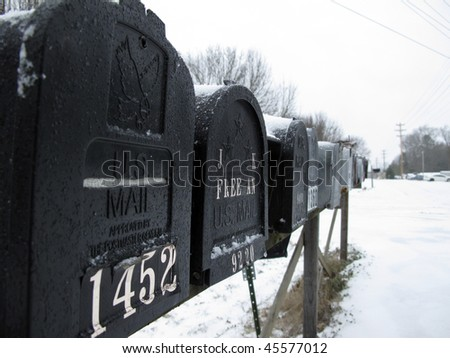 A row of mailboxes covered in snow from a late winter storm - stock photo