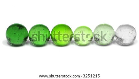 A Row of Marbles Fading from Dark Green to Nearly Clear