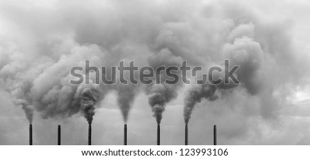 A row of metal chimney spewing heavy smoke polluting the sky.