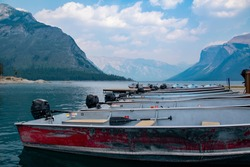 A row of motor boats is lined up at a dock, ready to take thrill seekers around the glacial Lake Minnewanka in Banff National Park, Alberta amid the Canadian Rocky Mountains.