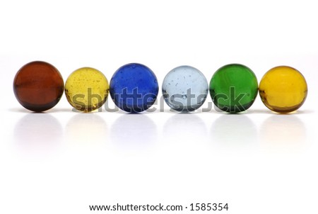 A Row of Multi-Colored Clear Glass Marbles on a White Background. - stock photo