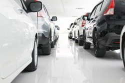 A row of new cars parked at a car dealership stock, New Japanese cars in showroom for show customers.