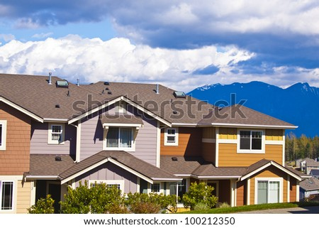 A row of new townhouses or condominiums with blue sky and clouds