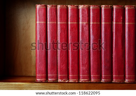 A row of old, battered, encyclopaedias on a shelf, with titles removed.  Red leather effect with gold striped trims.  Shelf has been darkened artificially to give impression of age.