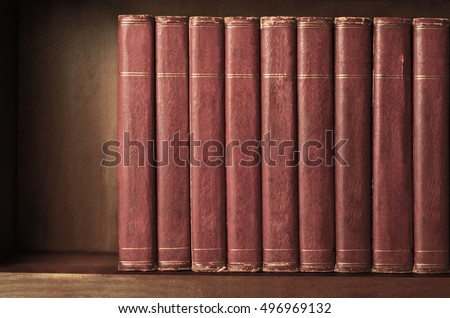 A row of old, battered, matching encyclopaedias (circa 1950s) lined up on a shelf, with titles removed to leave blank spines.  Red leather effect with gold striped trims.  Vintage effects applied. #496969132