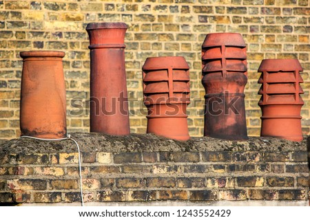 A row of 5 orange London chimney stacks made from clay o top of a brick building with a brick background
