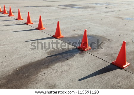 A row of orange traffic cones set on the road