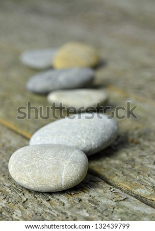 A row of pebbles lying on a wooden background with copy space