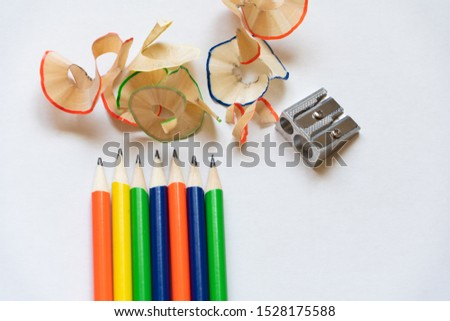 a row of pencils with sharpener and shaving