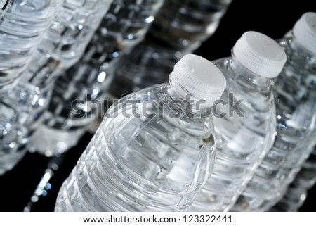 A row of plastic bottles of water on black background