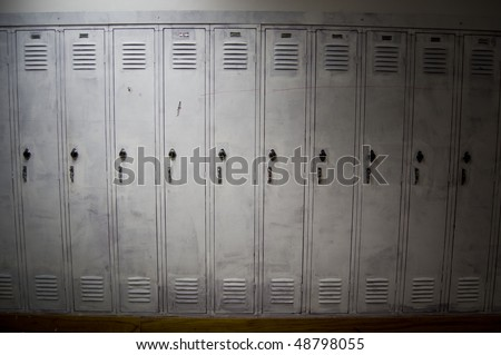 A row of poorly painted white lockers with shadows covering the sides of them. The lockers look old and worn down.