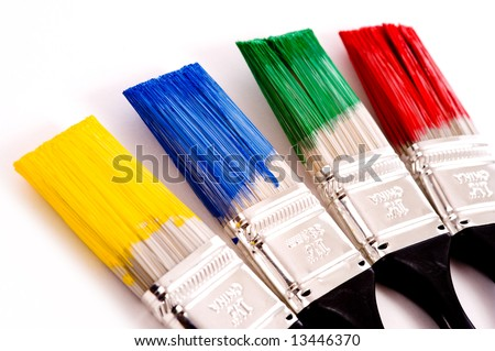A row of primary colored paint brushes on white background with copy space