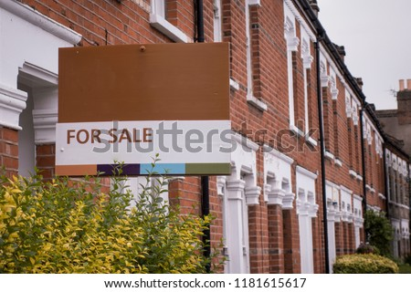 A row of red brick terraced houses with a 'for sale' sign in London #1181615617