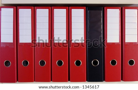 A row of red lever arch files on a shelf, with one black, un-marked one in their midst.