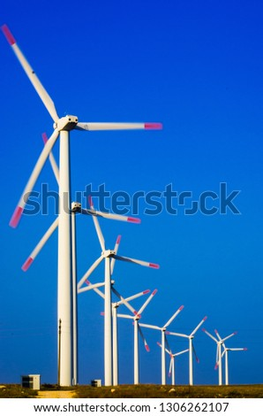 A row of rotating electric windmills. White wind turbines on a blue contrasty sky. #1306262107