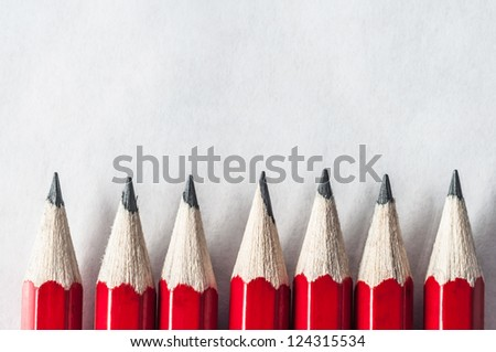 A row of roughly sharpened, grubby red pencils on textured art paper, bordering the bottom of the frame.  Lit and processed to give an old fashioned, vintage appearance.