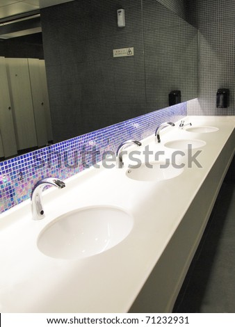 A row of sinks and taps in a public toilet (washroom)
