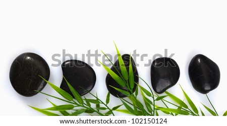 A row of spa massage stones and bamboo leaves on a white background with copyspace
