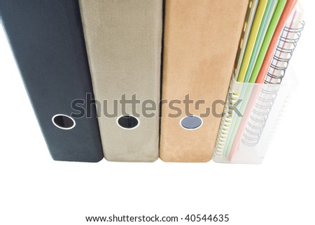 A row of suede lever arch ring binders - black, tan and faun and a clear plastic magazine rack containing cardboard files in blue; green; orange; yellow; white plus spiral bound notebook.