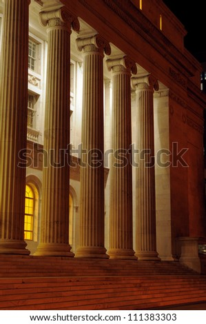 A row of tall roman columns at night at the Denver courthouse