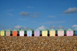 A row of ten colorful beach huts are in a line in the centre of the image in the foreground is a pebble beach above is a big blue sky with white clouds the sun is shining, Brighton, Sussex, UK.