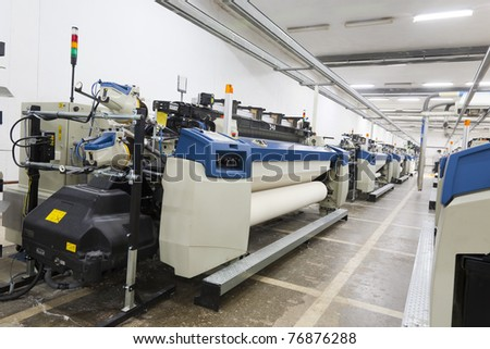 A row of textile looms weaving cotton yarn in a textile mill. - stock photo