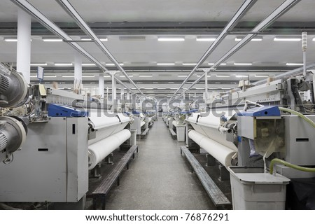 A row of textile looms weaving cotton yarn in a textile mill.