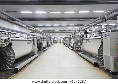 A row of textile looms weaving cotton yarn in a textile mill