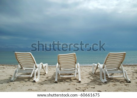 A row of three beach chairs overlooking the sea view