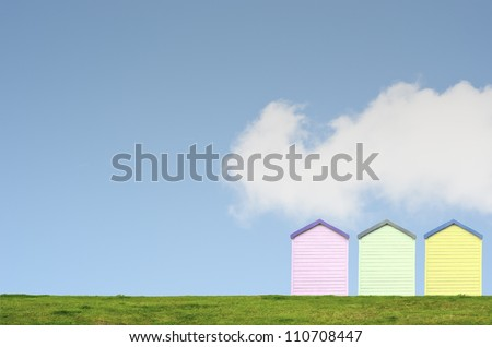 A row of three colourful beach huts on top of a grassy hill against a bright blue sky with white fluffy cloud. Copy space above and left.