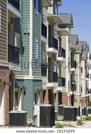 A row of townhouses with air conditioner compressors outside each one