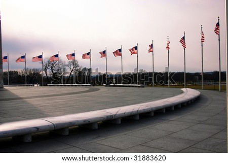 a row of US flags around the Washington Monument